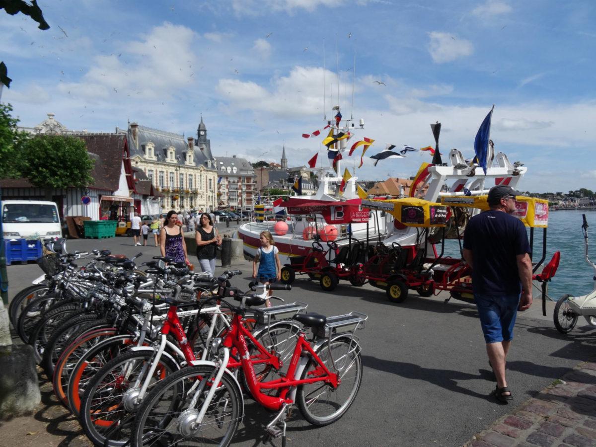 Vélos, rosalies et passants sur les quais de Trouville