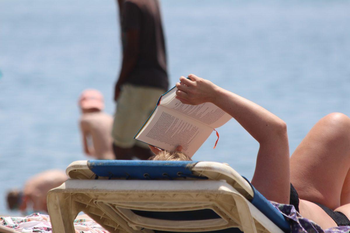 Instant bien-être - femme qui lit allongée sur la plage