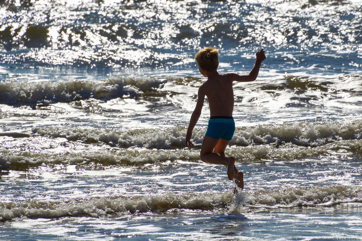 Petit garçon jouant dans les vagues